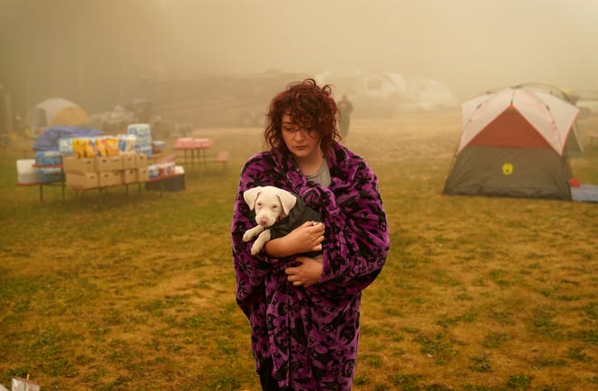 Shayanne Summers holds her dog Toph while wrapped in a blanket after several days of staying in a tent at an evacuation center at the Milwaukie-Portland Elks Lodge, on Sept. 13, 2020, in Oak Grove, Ore.