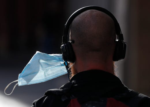 A man wears his face mask attached to his headphones in Prague, Czech Republic, Saturday, Sept. 19, 2020.