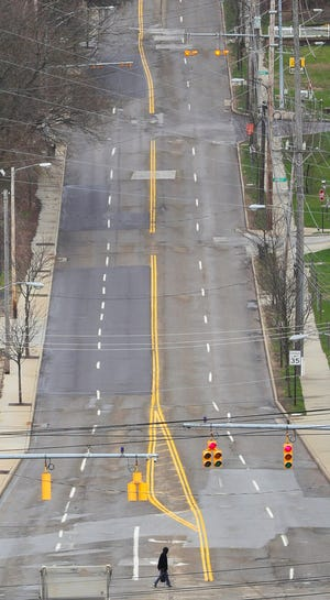 A lone pedestrian crosses a nearly empty Howard Street, Wednesday, April 1, 2020, in Akron, Ohio. Revenue from municipal income taxes in Ohio's six largest cities isnow threatened by a coronavirus-created, work-from-home movement that many experts say may reshape workplaces permanently. [Jeff Lange/Beacon Journal]