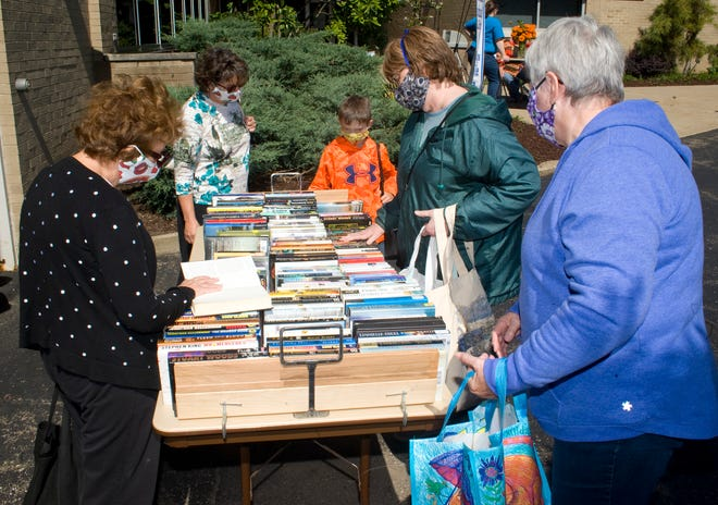 Visitors browse a table of books for sale at the Friends of Rodman Public Library book sale Sunday September 20, 2020. This years sale was a condensed version of the annual sale that is held during Carnation week but held later this year due to the COVID-19 pandemic. Michael Skolosh, Special to The Alliance Review