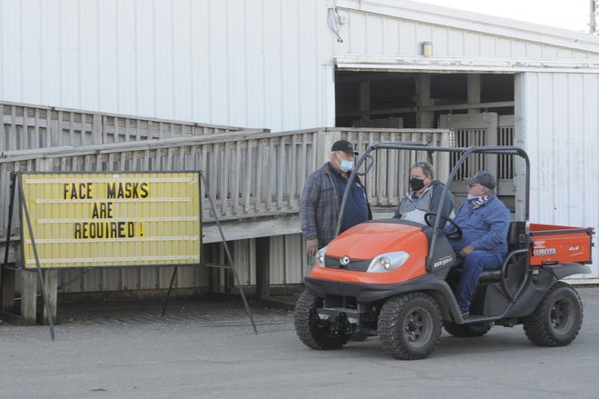 Marty Wesner, Alan Lifer and Bill Dillard meet outside the coliseum on Sunday morning at the Ashland County Fair. Masks are required in any indoor location and outdoors when six-foot distancing can't be achieved.