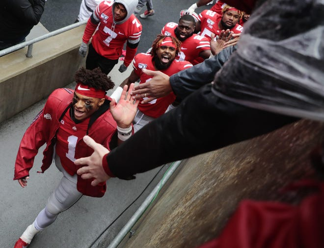 Ohio State quarterback Justin Fields greets fans as he heads to the locker room following a 38-7 victory over Wisconsin last October