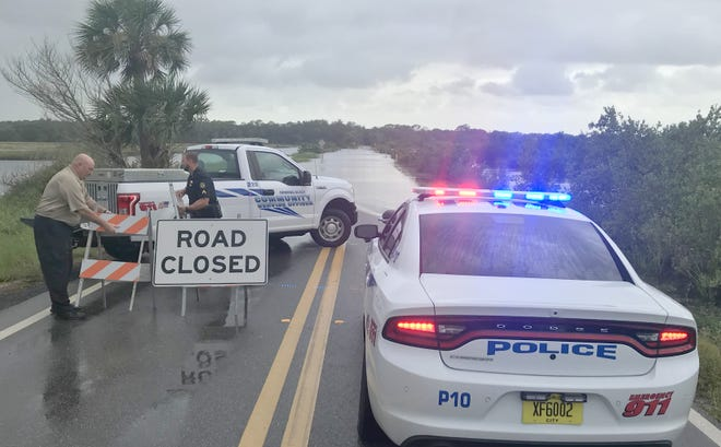 Police and a city worker set up a road block Sunday morning in the Loop in Ormond Beach. Saturday's and Sunday's rains have caused flooding in some areas.