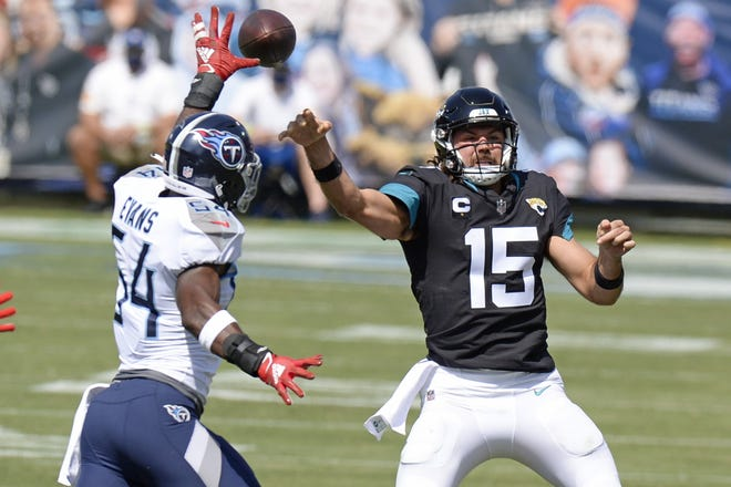 Jaguars' quarterback Gardner Minshew (15) gets a throw off as he's being pressured by Tennessee Titans linebacker Rashaan Evans in the first half of Sunday's 33-30 win by the Titans. (AP Photo/Mark Zaleski)