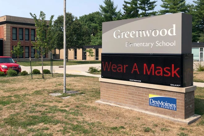 A sign outside of Greenwood Elementary School promotes mask-wearing on Thursday in Des Moines, Iowa. A dispute between Iowa's governor and the state's largest school district could mean summer school for students and crippling bills for the school system. Des Moines school officials have repeatedly refused to abide by Republican Gov. Kim Reynolds' order that districts hold at least half their classes in-person, saying it's not safe.