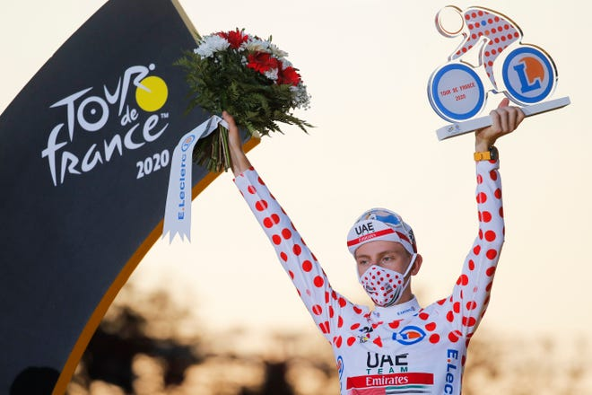 Tour de France winner Slovenia's Tadej Pogacar, who also won the best climber's dotted jersey, celebrates on the podium after the twenty-first and last stage of the Tour de France cycling race Sunday.