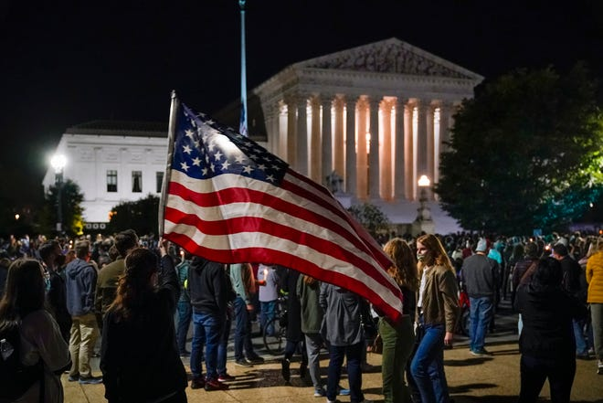 People gather at the Supreme Court in Washington on Saturday night to honor the late Justice Ruth Bader Ginsburg, one of the high court's liberal justices, and a champion of gender equality. Her death leaves a vacancy that could be filled with a more conservative justice by President Donald Trump.