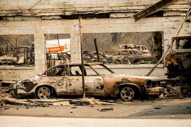 Scorched vehicles rest at an auto shop destroyed by the Almeda Fire in Talent, Ore., on Wednesday.  The Census Bureau is contending with several natural disasters as wildfires and hurricanes disrupt the final weeks of the nation's once-a-decade headcount.