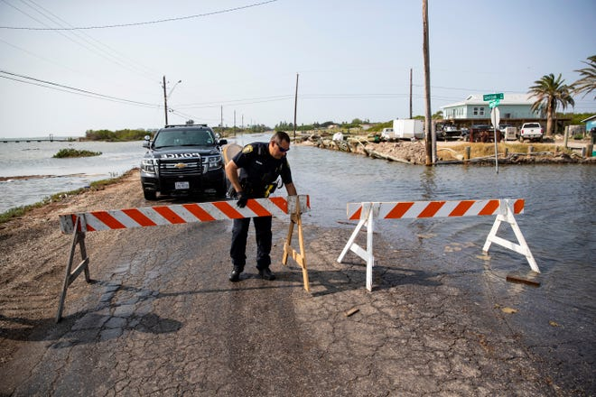 A Corpus Christi police office places a barricade to close Laguna Shores Boulevard after flooding on Sunday in Corpus Christi, Texas. Forecasters said Tropical Storm Beta is slowly churning through the Gulf of Mexico toward Texas and Louisiana, stirring worries that it could bring heavy rain, flooding and storm surge to a storm-weary stretch of the Gulf Coast.