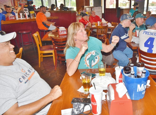 Tami Rodriguez and her husband Angel cheer on their respective teams at AJ's American Grill on Sunday. Tami, an avid Dolphins fan, might have attended the game in-person if not for COVID-19 restrictions on ticket availability.