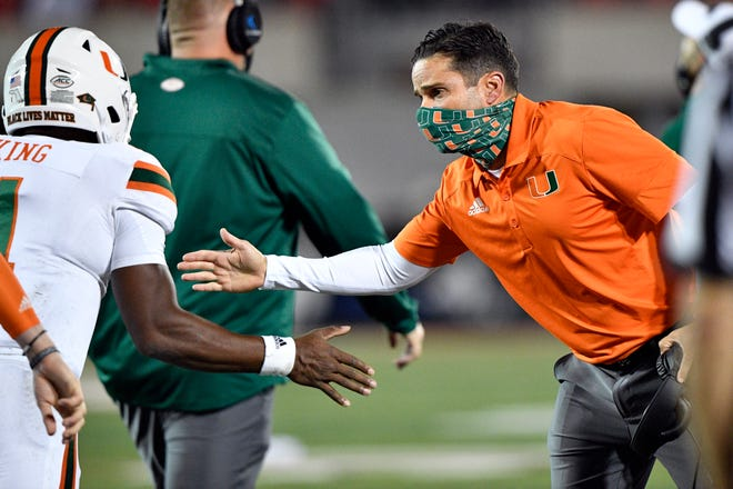 Hurricanes head coach Manny Diaz celebrates with quarterback D'Eriq King (1) during the first half of Saturday's win at Louisville. [Jamie Rhodes-ACC Pool]