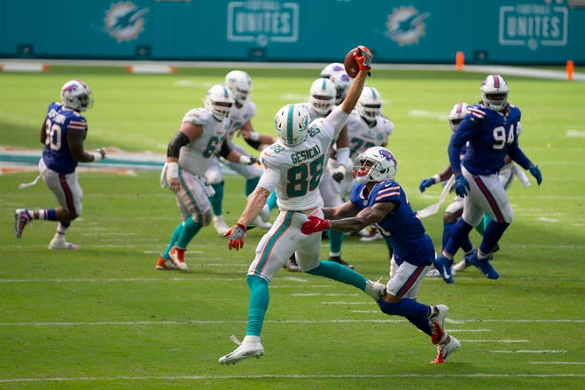 Dolphins tight end Mike Gesicki makes a one-handed catch against Bills strong safety Dean Marlowe (31) during Sunday's game at Hard Rock Stadium.