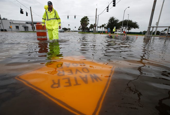 A Daytona Beach city employee works to reroute traffic around street flooding at Fairview Avenue and Beach Street in Daytona Beach on Sunday, Sept. 20, 2020.