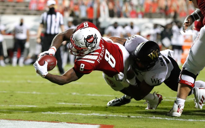 N.C. State running back Ricky Person Jr. (8) scores on a three-yard touchdown run as Wake Forest linebacker Ryan Smenda Jr. (5) defends during the second half of N.C. State's 45-42 victory over Wake Forest at Carter-Finley Stadium in Raleigh, N.C, Saturday, Sept. 19, 2020.