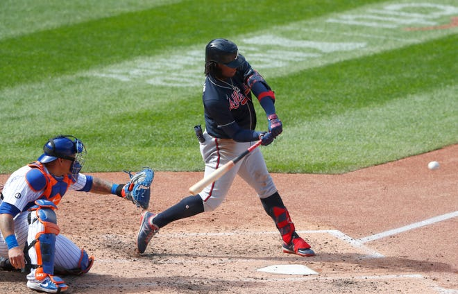 Atlanta Braves' Ronald Acuna Jr., right, hits a home run against the New York Mets during the sixth inning of Sunday's game.