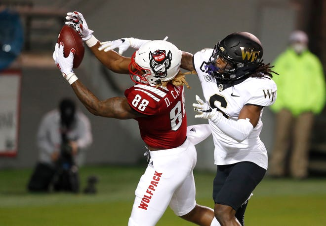North Carolina State receiver Devin Carter, left, hauls in a touchdown catch as Wake Forest defensive back Ja'Sir Taylor defends.