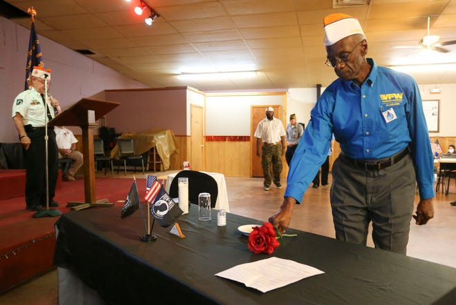 Members of the VFW Post 6022 in Cottondale honor the 82,000 American service men who are still listed as missing in action durning the annual commemoration of POW/MIA Day Friday, Sept. 18, 2020. Olan Truelove prepares to move a rose as he helps create the traditional table setting honoring the missing man. The Post also presented honors to the family of Tuscaloosa Police Investigator Dornell Cousette who was killed in the line of duty last September. [Staff Photo/Gary Cosby Jr.]