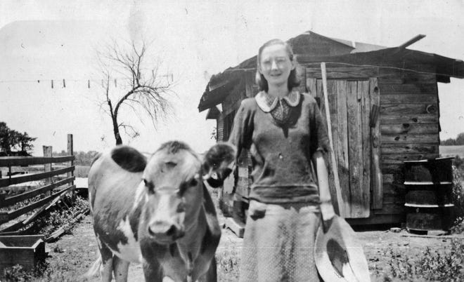 Aileen Kilgore Henderson with her favorite calf, Skinny Dugan, and the chicken house in background.