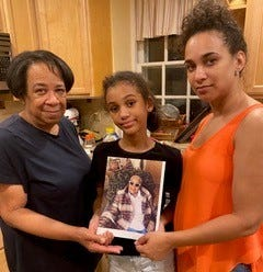 Daughter Lucia Herndon, great-granddaughter Jordan Dashields and granddaughter Melissa Horning Dashields pose for a photo holding a portrait of matriarch Lucille Dixon Herndon, who died of COVID-19.