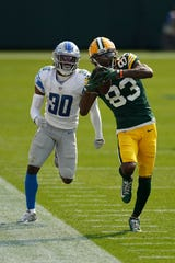 Green Bay Packers' Marquez Valdes-Scantling catches a pass in front of Detroit Lions' Jeff Okudah during the second half at Lambeau Field on Sept. 20, 2020 in Green Bay, Wis.