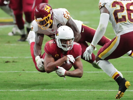 Arizona Cardinals wide receiver Larry Fitzgerald (11) is tackled by Washington Football Team linebacker Kevin Pierre-Louis after a catch during the third quarter at State Farm Stadium Sept. 20, 2020.