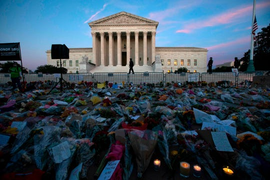 Flowers, candles, and signs are placed at a makeshift memorial outside the U.S. Supreme Court as people pay their respects to Ruth Bader Ginsburg in Washington on Sept. 19. President Donald Trump vowed to quickly nominate a successor, probably a woman.