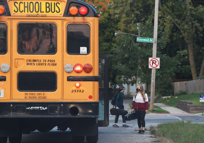 Ames school district students get on the bus to school on their first day of in-person class at Ninth Street and Ridgewood Avenue on Monday, Sept. 21, 2020, in Ames, Iowa.