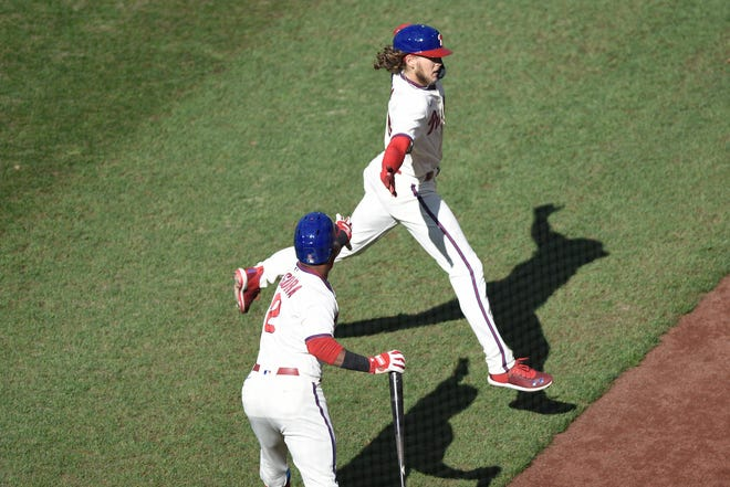 The Phillies' Alec Bohm, right, who scored a first-inning run Sunday, is congratulated by teammate Jean Segura.