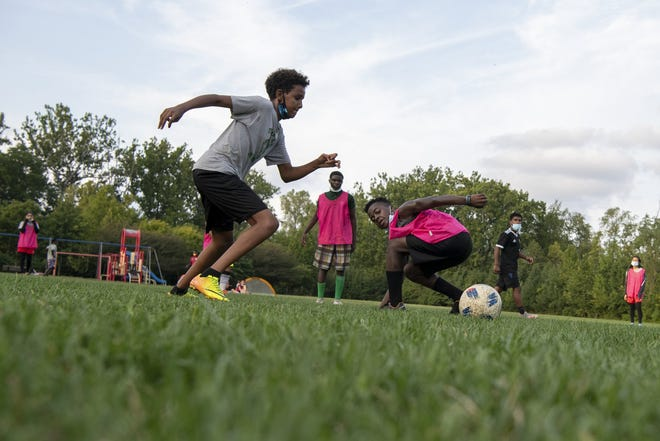 Students at Fugees Academy on Columbus' Northeast Side play soccer during practice on Sept. 10, 2020. Lewis Makor, the school's athletic leader, drives to neighborhoods where students live twice a week to hold practice near their homes since school is not holding in-person classes for those able to study remotely.