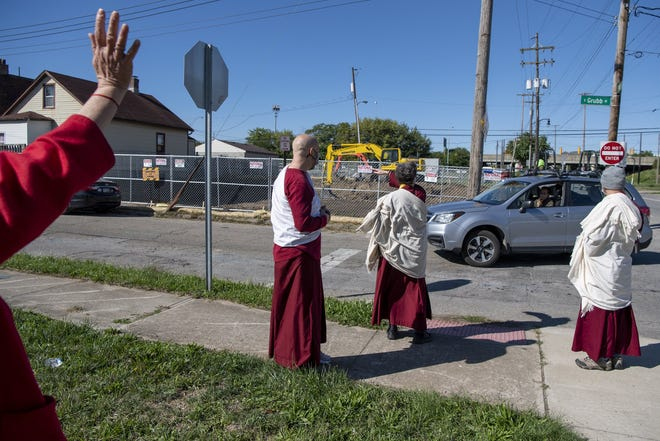 Teachers at the Columbus Karma Thegsum Choling wave as those attending Saturday's drive-thru celebration and thank-you event, which marked the recent start of the rebuilding of their Buddhist temple. The previous temple was destroyed in a January 2016 arson fire. [Gaelen Morse/Dispatch]