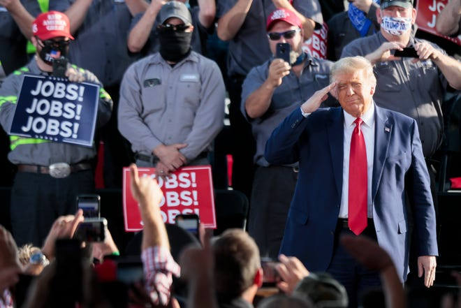 President Donald Trump salutes the crowd during a rally Monday at the Wright Bros. Aero Hangar at the Dayton International Airport in Vandalia.