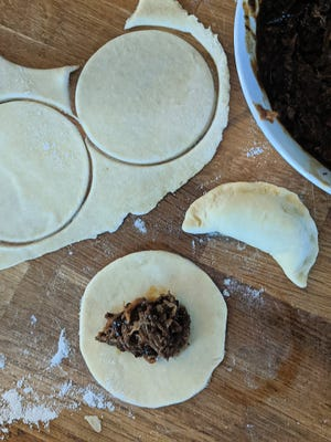 Homemade pierogies stuffed with pulled pork are served with coleslaw and pickles.