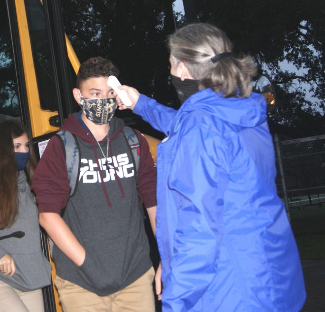 Angela Crawford, Master Teacher of Houma Jr. High School, finishes temperature checking students as they get off the morning bus to attend class.