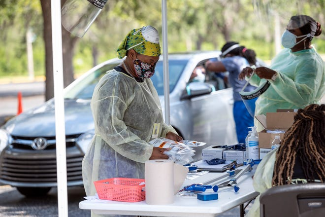 A health care worker packs tests for COVID-19 at Lake-Sumter State College in Leesburg. [Cindy Peterson/Correspondent]