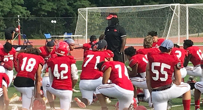 Van Horn football coach William Harris (in visor) speaks with his team following a devastating last-second 28-21 loss to Hogan Prep Saturday at William Chrisman High School.