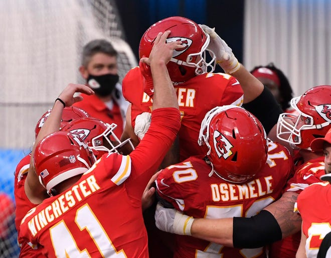 Kansas City Chiefs kicker Harrison Butker (7) celebrates is mobbed by teammates after kicking the game-winning 58-yard field goal against the Los Angeles Chargers during overtime Sunday at SoFi Stadium in Los Angeles.