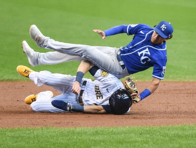 Kansas City Royals second baseman Nicky Lopez, top, tags out Milwaukee Brewers runner Christian Yelich after a high throw forced Lopez to leap for the ball in Yelich's path in the first inning of Sunday's game in Milwaukee. The Royals went on to lose 5-3.