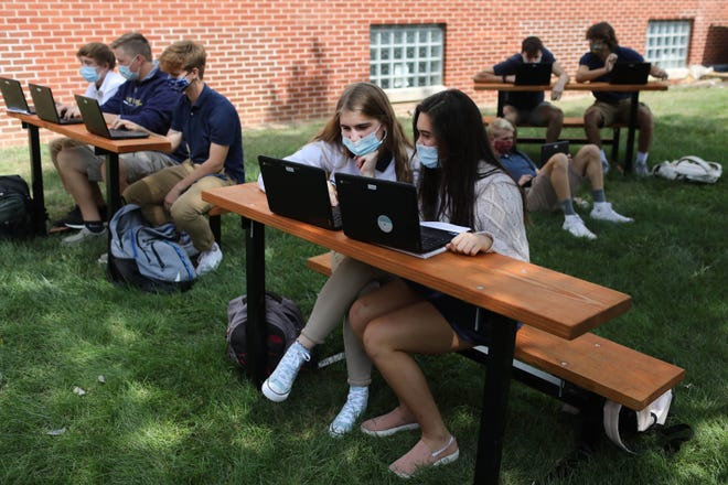 Jackie Meeker, 17, left, and Isabel Tjaden, 17, seniors in Anna Cavin's Burlington Notre Dame High School Spanish 4 class, work on an assignment Sept. 16 in the school's outdoor classroom, which is made up of a dozen tables recently donated by Chelsea Stevens, owner of Burlington Vintage and Co.