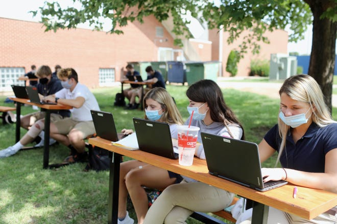 From front to back, Karli Artman, 17, Moly Johnson, 18 and Kerrigan Belger, 17, all seniors in Anna Cavin's Notre Dame High School Spanish 4 class, work on an assignment in the school's outdoor classroom Sept. 16 at the Burlington school. The Notre Dame school board decided on Thursday to transition the high school to an online-only format beginning Friday through Nov. 30 amid a rise in COVID-19 case among high school students.