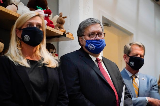 U.S. Attorney General William Barr, center, Georgia Gov. Brian Kemp, right and a Georgia Center for Child Advocacy staff member listen during a tour on Monday in Atlanta. (AP Photo/Brynn Anderson)