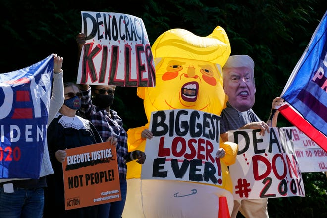 Protesters gather outside Trump National Golf Club in Sterling, Va., on Sunday before the departure of President Donald Trump's motorcade.
