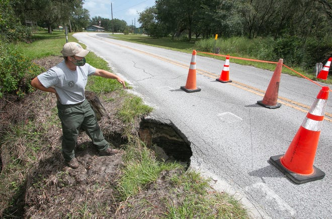 Paolo Pecora, an FWC freshwater fisheries biologist stationed at Tenoroc Fish Management Area, surveys the erosion damage undermining Tenoroc Mine Road leading into the area on Monday.
