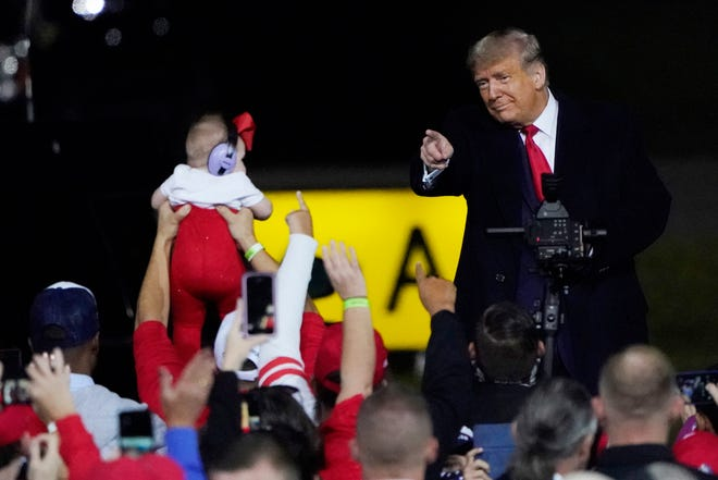 President Donald Trump wraps up his speech and points to an infant at a campaign rally at Fayetteville Regional Airport on Saturday in Fayetteville, N.C.