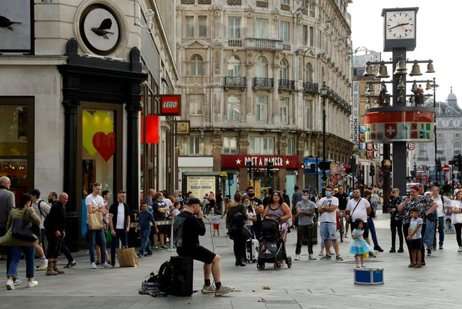 People listen to an entertainer perform in Leicester Square, central London, Saturday. Fresh nationwide lockdown restrictions in England appear to be on the cards soon as the British government targeted more areas Friday in an attempt to suppress a sharp spike in new coronavirus infections.
