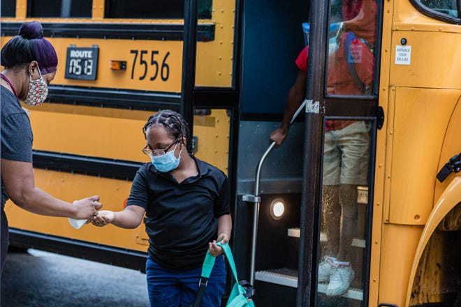Teacher's aide Andresa Holzandorf greets students and sprays hand sanitizer into their hands as they get off the bus Sept. 21 at Lincoln Elementary School in Riviera Beach. The students were returning to in-person classrooms for the first time after COVID-19 shutdown.