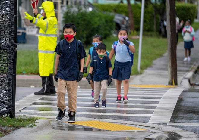 Crossing guard Paul Wilson stops traffic for students to cross the street on the first day of school at North Grade Elementary School in Lake Worth Beach on Monday.