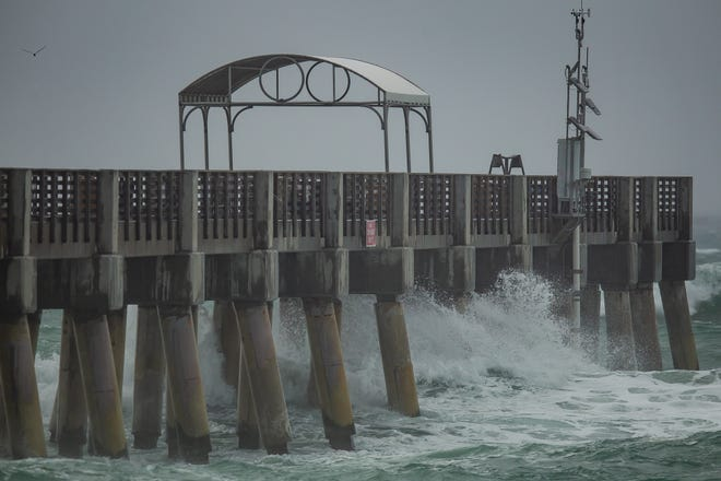 Wind-whipped waves churn Monday at William O. Lockhart Pier in Lake Worth Beach during the morning's rainstorm in central Palm Beach County.