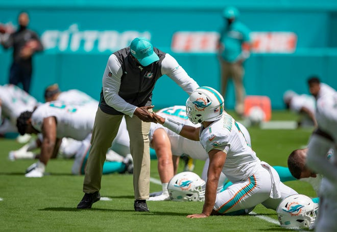 Miami Dolphins head coach Brian Flores shakes hands with Miami Dolphins quarterback Tua Tagovailoa (1) before game at Hard Rock Stadium in Miami Gardens, September 20, 2020.  [ALLEN EYESTONE/The Palm Beach Post]