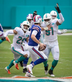 Bills quarterback Josh Allen is pressured by Dolphins safety Brandon Jones, left, and defensive end Emmanuel Ogbah (91), one of the team's key offseason acquisitions. Miami was called for a holding penalty on the play.