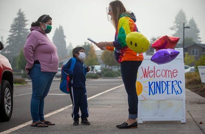 Grisalda Garcia and her son, Daniel Balbidares, listen to teacher Katie Keeler as she checks him in at Elizabeth Page Elementary School for his first day of kindergarten on Sept. 21 in Springfield.